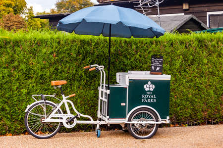 London, United Kingdom - September 15, 2017: Classic ice cream bicycle of the Royal Parks with blue parasol standing near the green natural fence 新聞圖片