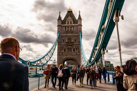 London, United Kingdom - September 14, 2017: Local people and tourists crossing the Thames river by the famous Tower bridge with its vibrant azure hanging metal constructions and high classic towers 新聞圖片