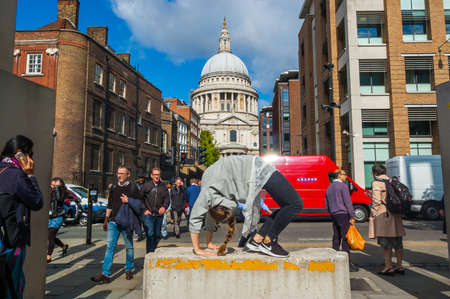 London, United Kingdom - September 18, 2017: Girl making gymnastic bridge pose on the stone in downtown of London full of walking people with Saint Paul Cathedral on the background
