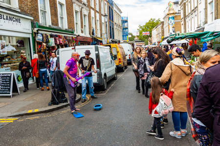 London, United Kingdom - September 16, 2017: Artists performing outdoors on the street. Two strange funny looking men performing on Portobello Road in London