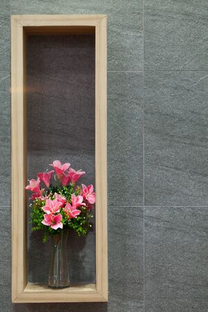 furniture design: Beautiful flowers in a glass vase on wall backgroundwith wooden frame