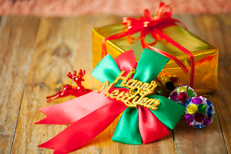 Golden gift box and red ribbon and Happy new year gift on wood background with space.