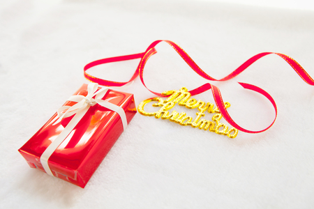 small red gift box and gold merry christmas text with red ribbon Stock Photo