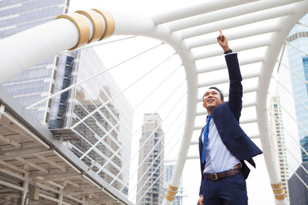 Businessman smiling and raising his fist with number 1 in the air, with office building background - business success, achievement, and win concepts