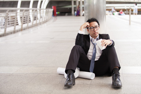 Stressful businessman or engineer sitting outdoor thoughtful thinking with hopeless Stock Photo