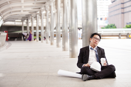 Stressful businessman or engineer sitting outdoor thoughtful thinking with hopeless Foto de archivo