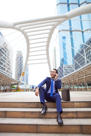 Businessman sitting on stair during callling the phone, with office building background - business success, achievement, and win concepts