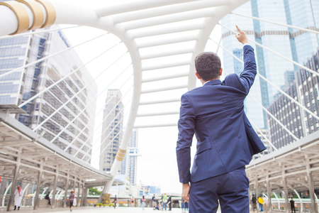 Businessman raising his fist  in the air, with office building background - business success, achievement, and win concepts Stock Photo