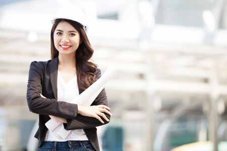 Smiling architect business woman with blueprints isolated portrait. Protect helmet.