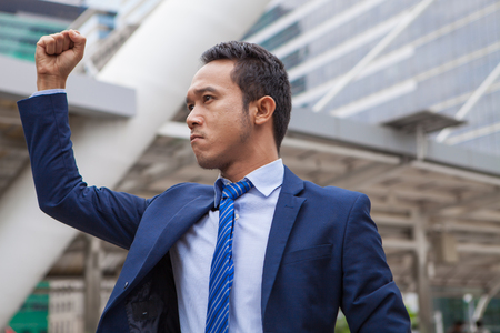 Businessman seriously  and raising his fist in the air, with office building background - business success, achievement, and win concepts
