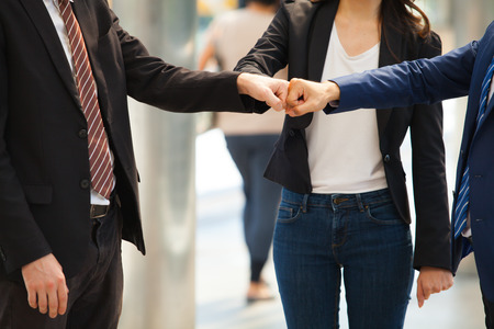 Close up of businessman making a fist bump on building with young woman in background. Business people wear suit do a fist pump together after good deal. Business success and teamwork concept.