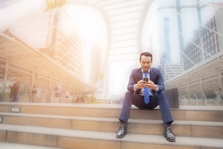 Businessman sitting on stair while looking on mobile phone, with office building background - business success, achievement, and win concepts Stock Photo