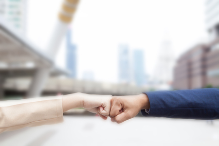 Close up of young businessman and businesswoman making a fist bump on building background. Business people wear suit do a fist pump together after good deal. Business success and teamwork concept.