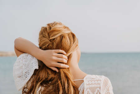 Young girl on the beach. With red long hair, standing with her back. Wedding hairstyle. Sea wedding concept.