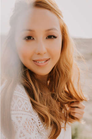 Young asian girl in a white wedding dress in a boho style, in the desert. With red long hair. With beautiful hairstyle and makeup. Makeup with nice false eyelashes. Sea wedding concept.