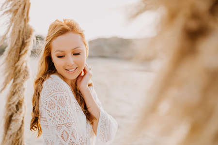 Young asian girl in a white wedding dress in boho style, on the beach. With red long hair, and makeup. Boho style wedding arch. Sea wedding concept. 免版税图像