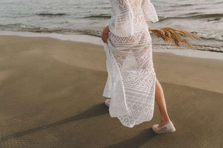 Bride with a bouquet of bamboo walks along the beach. Sea wedding concept. 免版税图像