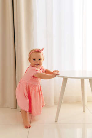 Child girl in a pink dress stands holding the table. 8 months old baby learns to walk and stand at the support. Stockfoto