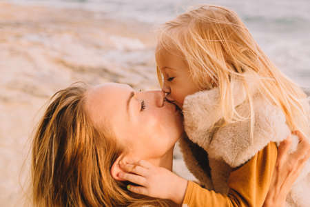 Mother with baby daughter next to the sea smiling. Baby girl with blonde hair, in a warm fur vest. Spring time, sun is shining. Travel abroad. Happy young family.