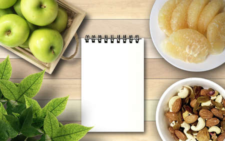 earth nut: Apples Grapefruit cocktail peanuts and white note book under maple leaves on wood background. Stock Photo