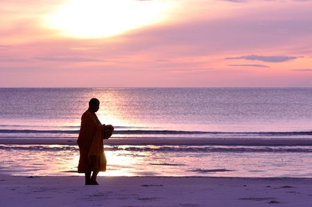 Monk ask for alms on the beach, Hua Hin, Thailand photo