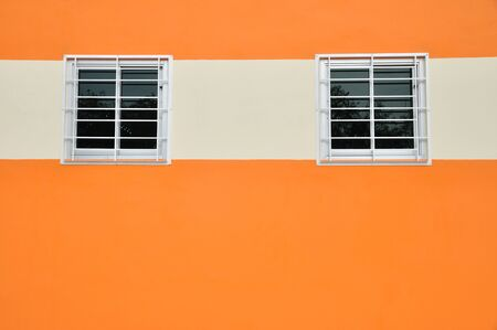 Square glass windows with cases on the orange wall Stock Photo - 21533137
