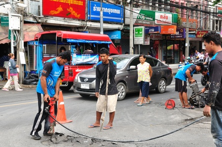 BANGKOK THAILAND - AUGUST 18  Unidentified Thai construction workers are drilling down into the street for construction the water main in Bangkok, Thailand  August 18, 2013