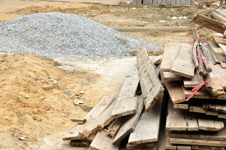Piles of woods, sand and gravel in a construction site