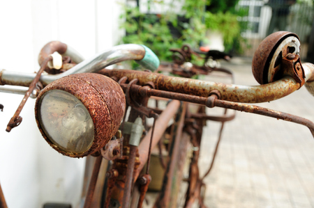 Antique and damaged bicycle parked next to wall
