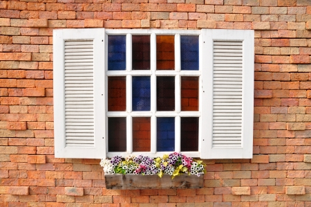 White window on red brick wall and color glass hang flowers pot  photo