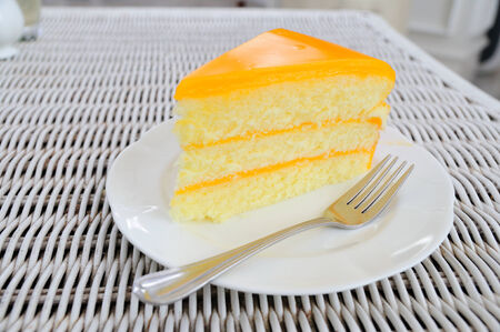 Orange layer cake on white plate put on rattan table.