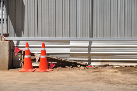 Orange traffic-cones around construction-area in front of corrugated iron for safety