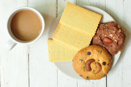 Various crackers, cookies on plate with coffee on wooden table  photo