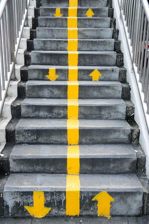 Flyover stairs with up and down yellow arrows separated by line  photo