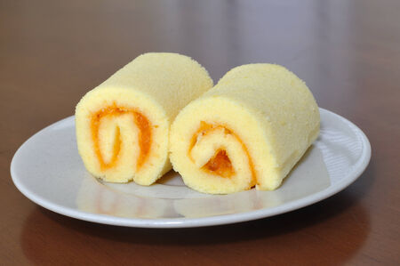 Mini orange jam rolls on wooden table  photo
