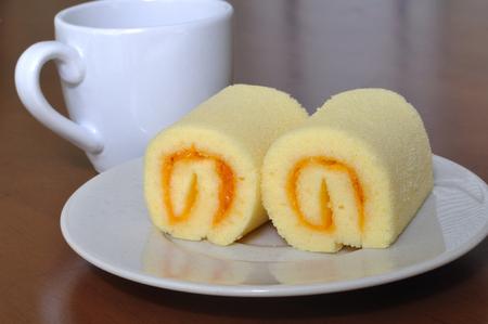Mini orange jam rolls on wooden table  Stock Photo