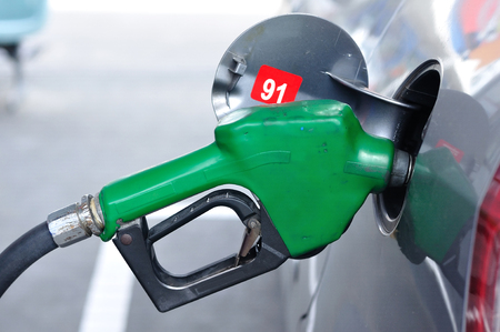 Green gasoline nozzles figure filling into tank