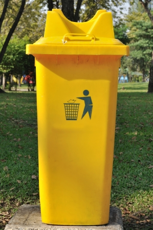 Yellow public bin in garden photo