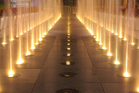 Multiple jets of water in a fountain, lighting show on ground in night time