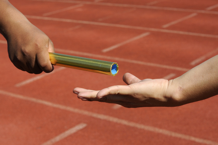 teammates: Relay-athletes hands sending action