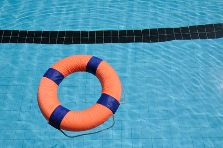 Orange swim ring with deep blue trim floating on water  Stock Photo
