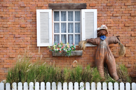 Local scarecrow next to classic white window  photo