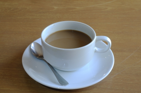 White coffee-cup with spoon on wooden table  photo
