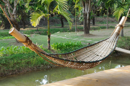 Old bamboo hammock hanging in garden photo