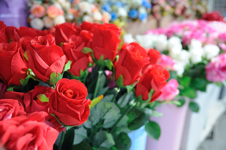 artificially: Many red roses showing in pot, artificially.
