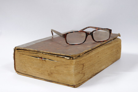 Ancient book with glasses, education concept. photo