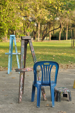 Various wooden easels with plastic chairs in public garden photo