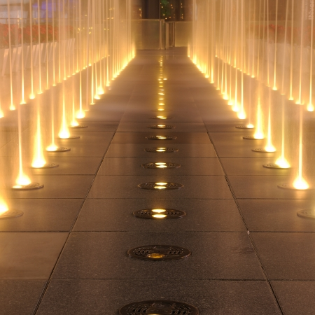 Multiple jets of water in a fountain, lighting show on ground in night time. photo