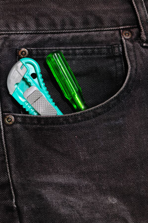 boxcutter: Box-cutter and screw driver in jean pocket. Stock Photo