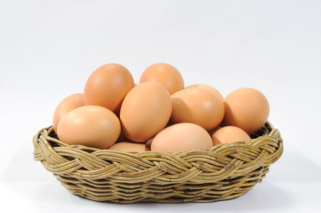 eggs in rattan basket on white table. photo